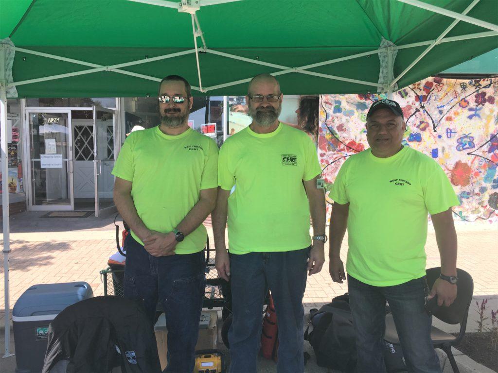 Brian Freund, Kurt Freund, and Francisco Gomez standing at CERT tent.