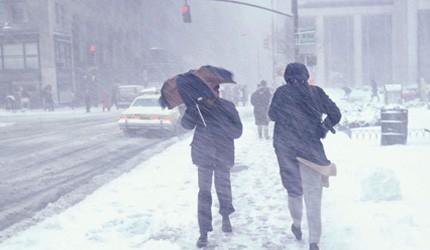 Two people walking in a snow storm on sidewalk