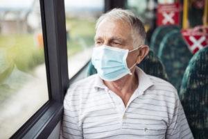 Senior wearing a mask on bus