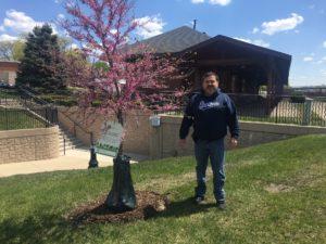 Mayor Pineda standing next to redbud tree